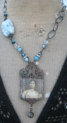 """Vintagephoto of a beautiful young woman soldered under glass. Attached and aged filigree, vintage lace on back, Sterling and Marcasite bead hangs from the bottom. Blue quartz beads, Aurora Borealis beads, clear quartz, blue rhinestone balls, oxidized Sterling chain, metal hook, Religious medal. Length 20""""  $225  Pendant 2-1/4"""" x 1-1/4""""."""