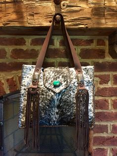The Market Tote with a rounded flap and turquoise stone, straps with vintage sterling silver pieces, D loops with fringe, and exterior pockets lined in suede. gowestdesigns.us