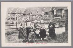 Een groep kinderen in dracht poseren met op de achtergrond houten woonhuizen en waslijnen. 1893-1910 #NoordHolland #Marken
