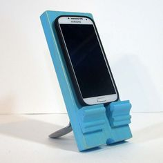 This cell phone holder and charging stand is made from wood and recycled stainless steel spoons with a rustic sanded edge finish in aqua blue.