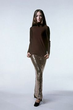 1968 Windsor Eliot in a chocolate brown silk jersey turtleneck worn with a long slim skirt covered in gold paillettes by Norman Norell