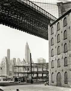 May 22, 1936. Warehouse district, Water and Dock Streets, Brooklyn, looking west under Brooklyn Bridge to Lower Manhattan.