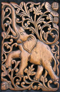 carved teak wood panel of an elephant with trunk raised set in a framework of lattice scrolls
