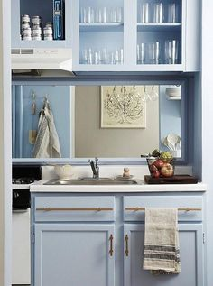 White hand towels and appliances, framed artwork, and gleaming brass hardware pop against the new soft blue paint color of the kitchen's walls and cabinets.