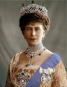 Queen Mary wearing the Delhi Durbar tiara in its original form: a circlet of brilliant-cut diamonds, mounted in gold and set in platinum, and arranged in a pattern of forget-me-nots and lyres. When the tiara was first made in 1911, it was topped with five drop-shaped cabochon Cambridge emeralds, that arose as spikes from the tiara. later the emeralds were removed and 2 satellite diamonds from the Cullinan were incorporated.  See the modern form on the Tiaras I board.