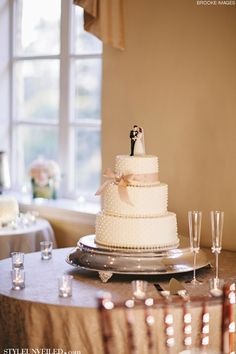 White Wedding Cake with Pearl Detailing and a Pink Bow / Brooke Images / Epping Forest Yacht Club / www.styleunveiled.com