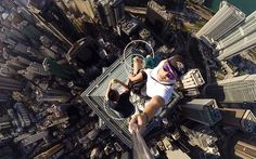 """Rooftopping photographers Andrew Tso and Daniel Lau recently climbed to the very top of The Center, the fifth tallest skyscraper in Hong Kong. While at the top, Lau pulled out his """"selfie stick"""" (AKA a retractable handheld monopod) and captured the crazy shot above."""