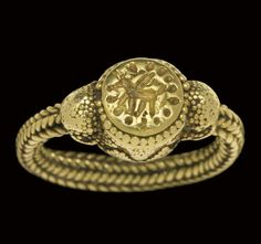 Western Asiatic Electrum Finger Ring, Circa 9th-7th Century BC  The hoop composed of wire ropes, merging with the circular box bezel, granulated bosses at the join, the bezel with triangles of granulation on the sides, beading at the top, the upper surface engraved with a winged quadruped in profile encircled with dots.