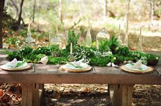 Greenery Filled Wedding: Green table centerpiece with moss, ferns, cloches, and bottles with candles.