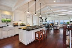 White cabinets, dark wood floors, open kitchen with vaulted ceiling.