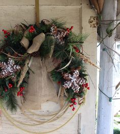 Cowboy Christmas wreath Lariat rope wreath with Christmas greenery, berries, holly, pinecone star ornaments and a burlap bow