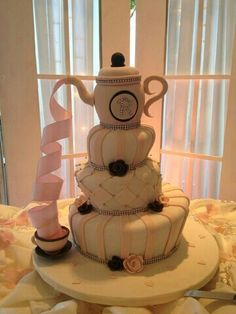 Sit tea pot atop something tall and have ribbon trail down into cup. Bridal shower idea... Tea cup theme