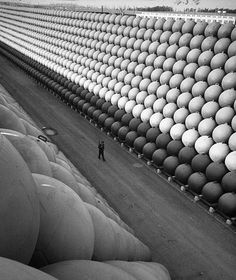 A lone security guard walks down U.S. Highway 101 among towering stacks of hollow iron floats, from which iron antisubmarine nets were held up to protect the U.S. ports in California during the last war.