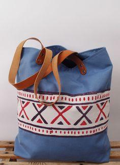 Tragetasche aus hell- bis mittelblauer Baumwolle mit aufgenähter Musterbordüre und genieteten Lederhenkeln. Die Tasche ist mit dunkelblauer Baumwo...
