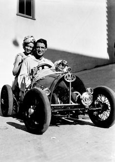 Cary Grant zips around the Paramount Studios lot with a Hollywood starlet on a mini race car, early 1930s.