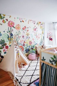 sweet floral wallpaper and Moroccan rug mix in this kids room!