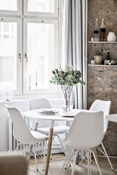 white dining table and chairs. brick wall.