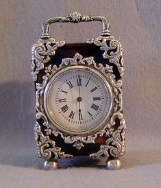 A fine small antique English silver mounted tortoiseshell carraige clock. Silver feet, hinges, handle, dial surround and applied silver rococco mounts to the 8 corners. Marked for London 1910 with makers mark wwwp. 8 day lever escapement movement. Key wound..........Gavin Douglas Antiques