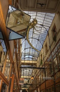 """The """"Passage du Grand Cerf""""- is one of the prettiest in Paris. With its 3 floors and heighth of the glass roof at 11,80 metres it is the highest of Paris. It has 33 shops mainly dedicated to decoration and antiques, but does also have a brazilian restaurant. Built in 1835, this was the departure point for the postal wagons. Etienne Marcel is the nearest metro station."""
