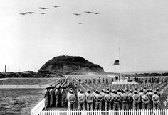 1947-- Two Year anniversary of the Battle of Iwo Jima Memorial services are conducted at an Iwo Jima cemetery on Feb. 20, 1947. Four-engined military planes soar overhead and the U.S. flag is at half staff in honor of those who died in the 1945 invasion of the then Japanese held island. Mt. Suribachi is in the background. (AP Photo/Joe Rosenthal)
