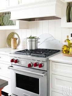Layering a shapely piece of marble over tongue-and-groove siding creates a layered look for this backsplash idea that honors the 1897 Victorian home that once stood on this lot. The owner wanted to restore a feeling of the historic home, but in a simpler form. The distinctive kitchen backsplash design, combined with the wood paneled backdrop, adds dimension to the wall.
