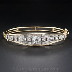 Art Deco Bangle Bracelet - 1.10 carat high-quality European-cut diamond blazing from within a square platinum setting. This scintillating stone is presented atop an exquisitely fashioned geometric design composed of matte-finished platinum arrayed with smaller sparkling European-cut diamonds - bringing the total diamond weight to 2.00 carats. The hinged, openwork bangle bracelet is crafted in 18 karat yellow gold.