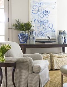 A blue abstract art piece is mounted above an espresso stained farmhouse console table accented with blue ginger jars and positioned beige trellis ottomans. Traditional Interior, Painted Chairs, Rustic White, White Rooms, Room Accessories, Sophisticated Style, Living Room Decor, Living Rooms, Living Spaces