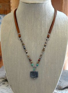 A long handmade multi-gemstone pendant necklace with a tribal style. Features a pewter totem warrior on a gemstone and leather lace necklace. Stone beads include Picture Jasper, Red Jasper, Red Creek Jasper, Sunstone, Labradorite, and Kingman, AZ turquoise with a scattering of silver beads throughout. All of this is attached to light tan leather lace and secured in the back with a silver tone alligator clasp.  Necklace measure 24 long and the pendant adds 1-1/2 to the length.  This will look…