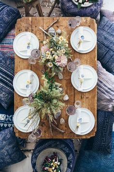 Indigo and navy patterned pillows with a rustic wedding table setting featuring lush floral centerpieces with muted hues.