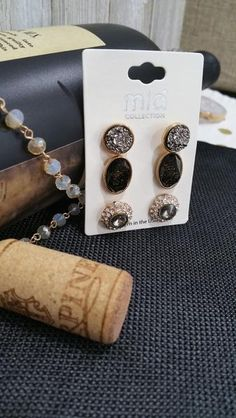 Gold tone three pair earring set with faux druzy studs, faceted black studs, and gray rhinestone studs.