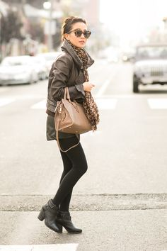 Amazing - black pants, ankle booties, satchel bag, warm up turned jacket, huge scarf, which matches her sunglasses