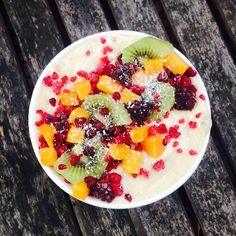 Banana smoothie bowl topped with raspberries, kiwi fruit, mango, blackberries & coconut