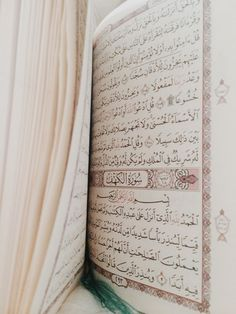 An open book of Quran showing the beginning of Surat al-Kahf (18:1-3)