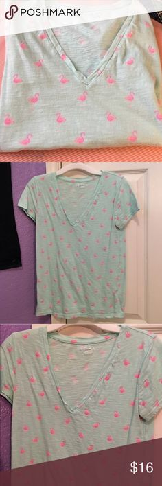 Flamingo Tee 🌴 Green flamingo v-neck tee. Used but in good condition. PLEASE READ THE ENTIRE DESCRIPTION BEFORE PURCHASING! 🚫 NO TRADES. NO HOLDS. NO MERC@RI 🚫📩 I only respond to offers made through the offer button 📩  🙋🏼Questions? Just ask! Serious inquiries only please. EVERYTHING MUST GO!! 💁🏼 Merona Tops Tees - Short Sleeve