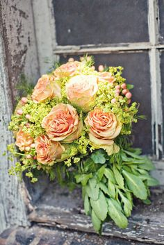 gorgeous colors. Le bouquet nostalgique.  A peach bouquet of oversized summer garden roses, alchemilla and berries harkens back to a romantic, bygone era of 1950s vintage chic style.  A natural wrap of soft pale green foliage imparts an organic, natural feel and is quintessentially Parisian.