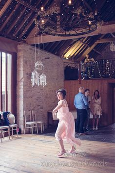 Bridesmaid dances under fairy lights at Kingston Country Courtyard Wedding Photographs. Photography by one thousand words wedding photographers