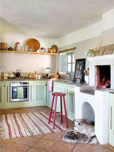 Cocina rústica con baldas de madera y menaje de barro