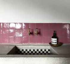pink tiles and a black and white checkerboard sink
