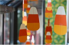 20 Spooktacular DIY Halloween Decorations: Hanging Candy Corn Window Decoration