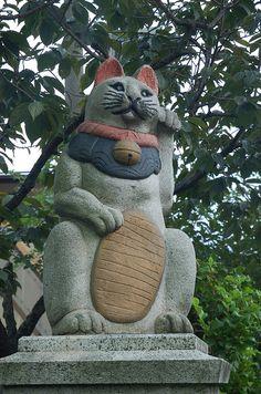 Maneki Neko. Painted Stone Statue. Toshima, Tokyo, Japan.