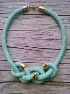 A aqua climbing rope necklace braided with gold beads.