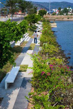waterside park by MIA Design Studio runs alongside a lake in Vietnam