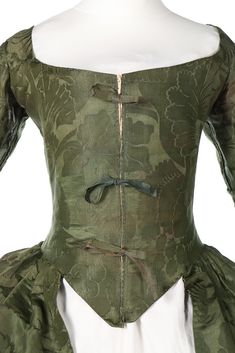 Detail front bodice, robe à l'Anglaise, England (Spitalfields), ca. 1770, fabric: ca. 1743. Forest-green silk damask, woven with large scale flowerheads, berries and leaves, with ribbon-tied front bodice, cuffs edged in self-fringing.