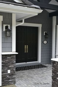 LOVE the black painted double front door. Painted shingles are Chelsea Gray by … LOVE the black painted double front door. Painted shingles are Chelsea Gray by Benjamin Moore. White trim and dark charcoal ledgestone. Chelsea Gray, Design Exterior, House Paint Exterior, Home Exterior Colors, Gray Exterior Houses, Black Trim Exterior House, Grey House Exteriors, Stone On House Exterior, Exterior Paint Ideas