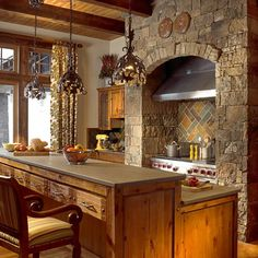 Beautiful Rustic Kitchen ~ I love all the cabinetry and all the other woodwork, the stonework around the range and vent-hood, the slate back splash and the awesome pendant lighting.
