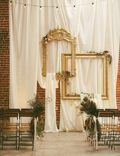 hanging empty gold frames + draped fabric