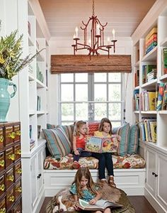 what's not to love about this picture? built-ins, book shelves, books, color, white, and the of course the sweet girls reading together.