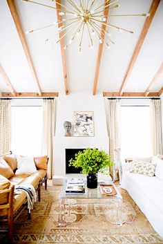 Neutral living room with wooden beam ceiling and lucite coffee table