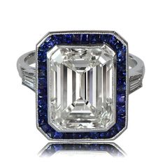 Diamond-and-Sapphire-Art-Deco-Style-Engagement-Ring-10362-T-View  beautiful Diamond and Sapphire Engagement Ring featuring a 8.01ct emerald cut diamond, and surrounded by a row of fine Ceylon sapphires. Mounted in a handmade platinum mounting, the center diamond is approximately 8.01ct, K color, VS clarity. This diamond is very lively stone with a beautiful cut. The ring is accented by one baguette diamonds on each side.