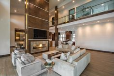 Warm neutral tones and streamlined furnishings help this large great room flow as one. The custom two story chimney is made with organic wood and stainless steel accents and becomes an easy center piece for the whole home.